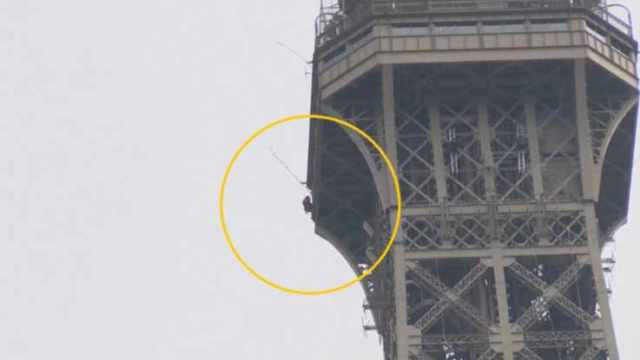 tour eiffel uomo arrampica torre